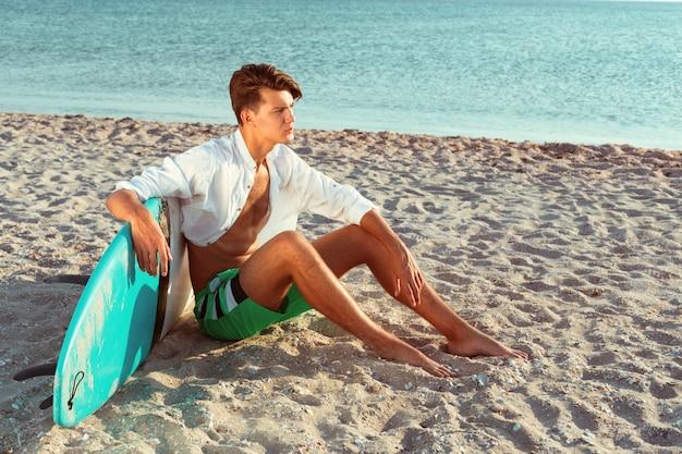 Uomo che si rilassa dopo aver surfato