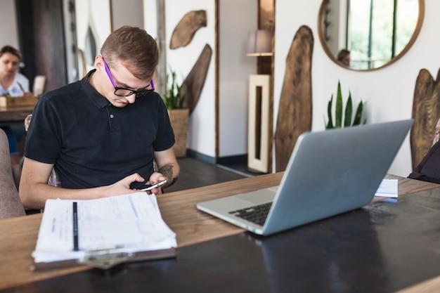 Uomo che si siede con lo smartphone nella caffetteria