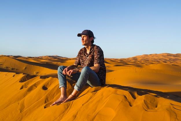 Uomo che si siede in cima alla duna nel deserto