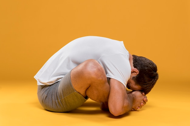 Uomo che si siede nella posa di yoga della curvatura di andata