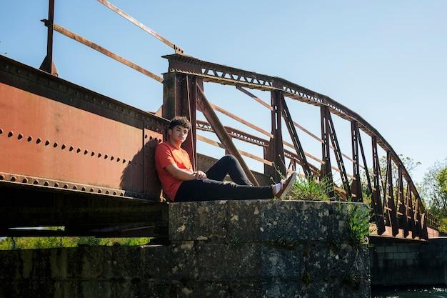 Uomo che si siede sul pilastro del ponte che guarda l'obbiettivo