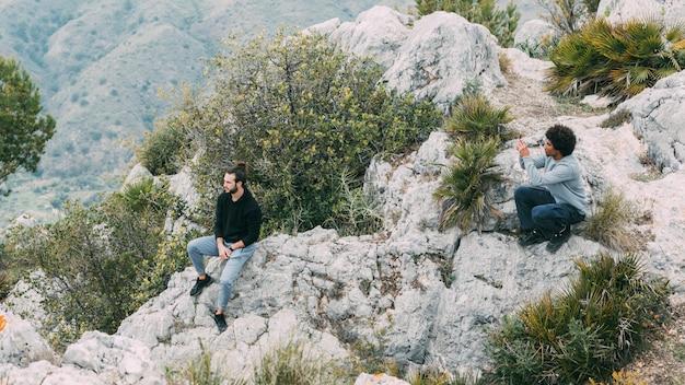 Uomo che si siede sulla roccia in natura