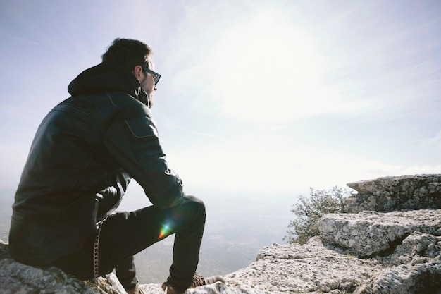 Uomo che si siede sulla roccia