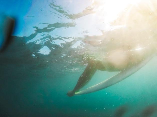 Uomo che si trova sulla tavola da surf in acqua blu
