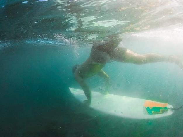 Uomo che si tuffa con tavola da surf sott'acqua