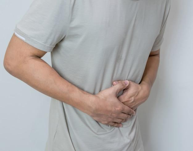 Uomo che soffre di mal di stomaco con entrambi i palmi intorno alla vita per mostrare dolore e lesioni sulla zona del ventre