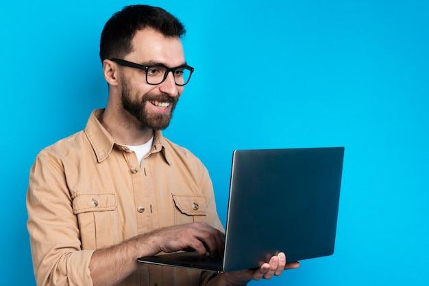 Uomo che sorride mentre esaminando computer portatile