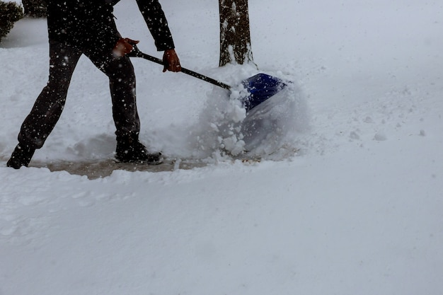 Uomo che spalava la neve dal marciapiede davanti a casa sua dopo una fitta nevicata