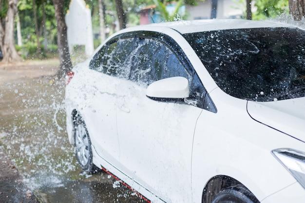 Uomo che spruzza acqua all'automobile bianca per lavare
