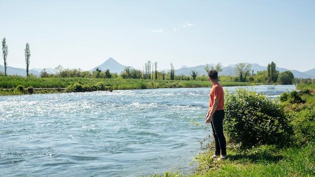 Uomo che sta vicino al fiume che scorre naturale