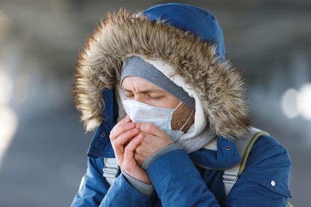 Uomo che starnutisce, tossisce, indossa una maschera protettiva medica.