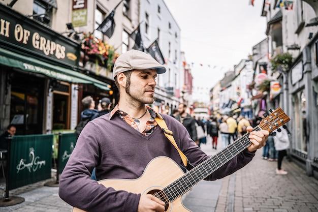 Uomo che suona la chitarra acustica in una strada pedonale.