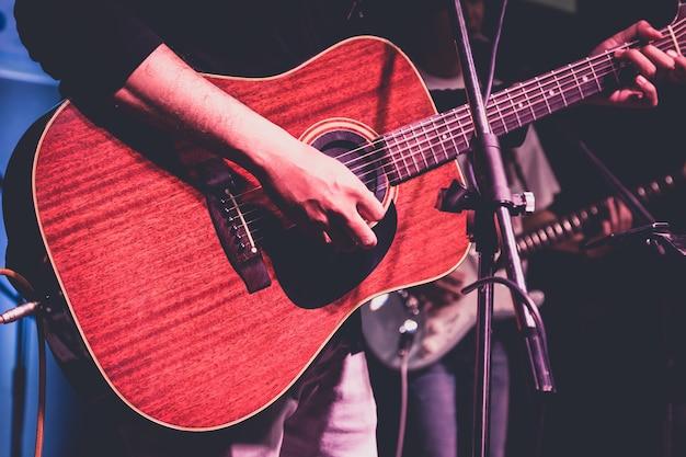 Uomo che suona la chitarra acustica