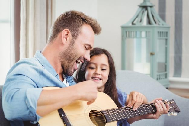 Uomo che suona la chitarra con sua figlia a casa