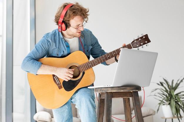 Uomo che suona la chitarra e indossa le cuffie