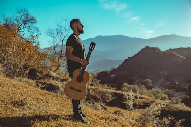 Uomo che suona la chitarra in montagna