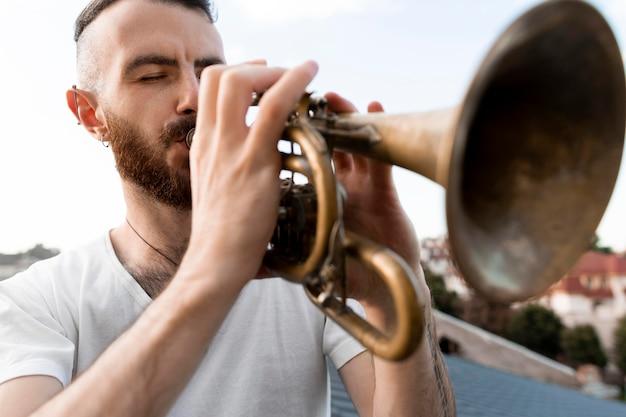 Uomo che suona la cornetta all'aperto