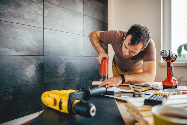 Uomo che taglia il legno con il puzzle elettrico