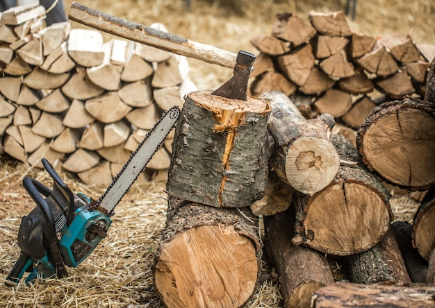 Uomo che taglia legno a pezzi con una motosega