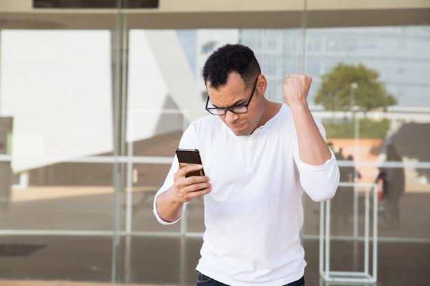 Uomo che termina la telefonata, riceve notizie, celebra il successo