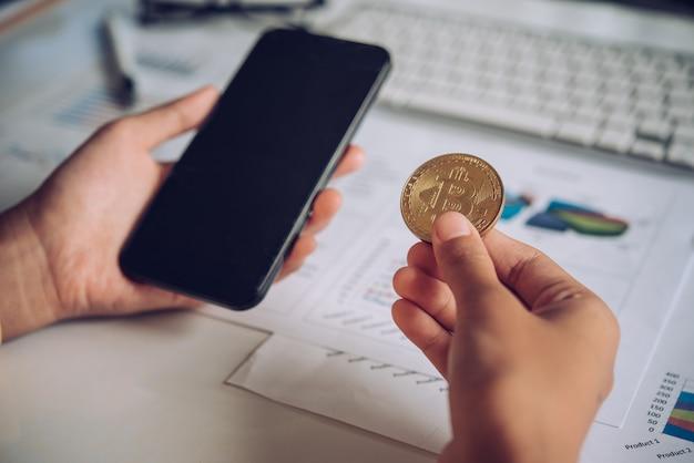 Uomo che tiene bitcoin e sfondo con smartphone