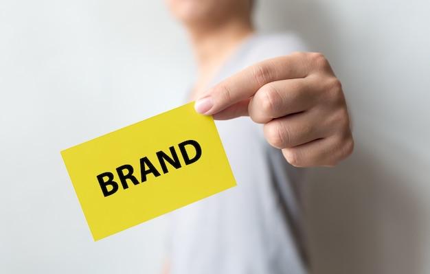 Uomo che tiene cartellino giallo e parola marca. costruzione del marchio per il concetto di successo