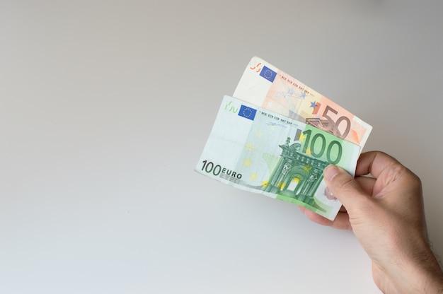 Uomo che tiene centocinquanta banconote in euro nelle sue mani