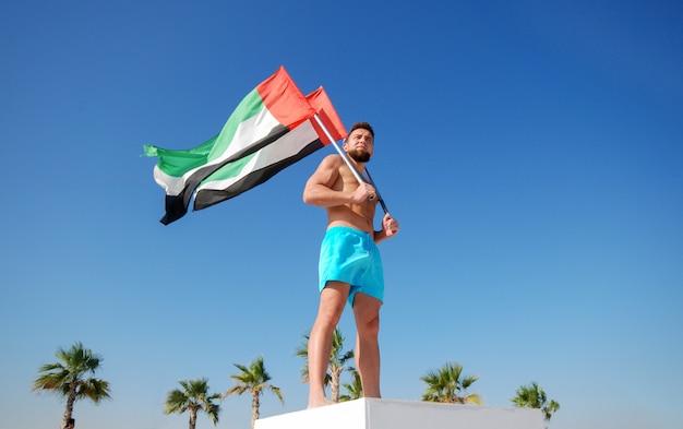 Uomo che tiene due bandiere degli emirati arabi uniti