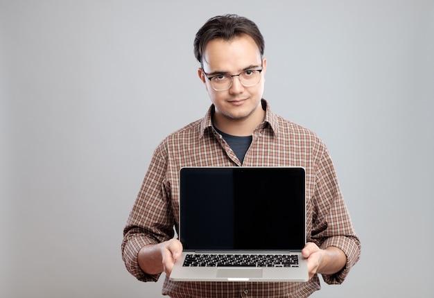 Uomo che tiene e che mostra computer portatile