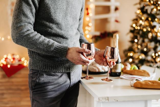 Uomo che tiene i bicchieri di vino e champaigne