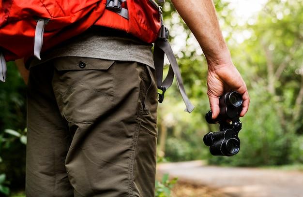 Uomo che tiene il binocolo nella foresta