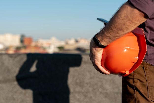 Uomo che tiene il cappello duro arancione