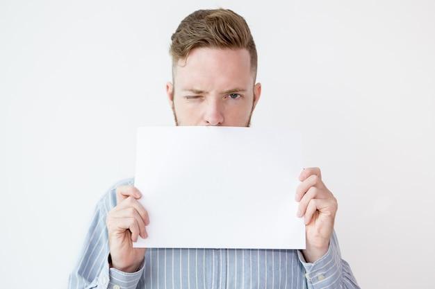 Uomo che tiene il foglio di carta vuoto dell'annuncio