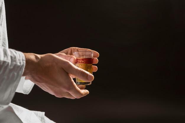 Uomo che tiene il fondo tradizionale del nero del tè