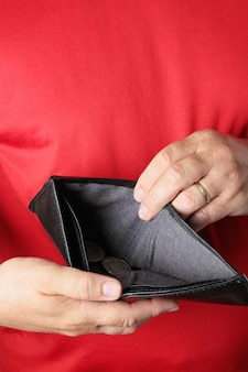 Uomo che tiene il portafoglio vuoto. inganno, idea dei debiti