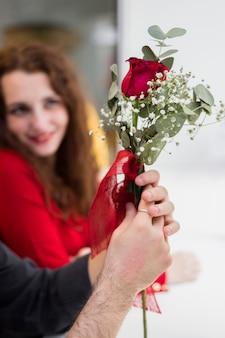 Uomo che tiene il ramo di rosa rossa in mano