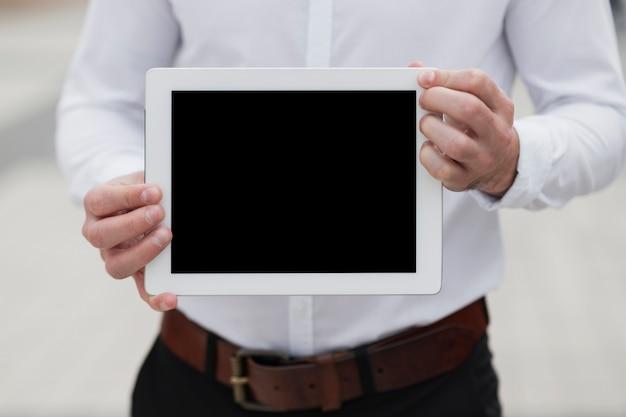 Uomo che tiene ipad mock-up vista frontale