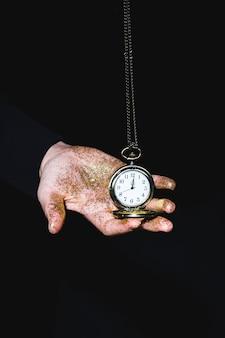Uomo che tiene l'orologio da tasca