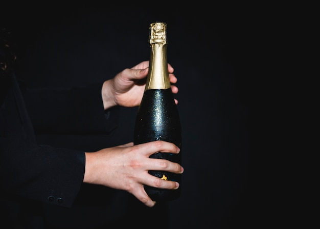 Uomo che tiene la bottiglia di champagne