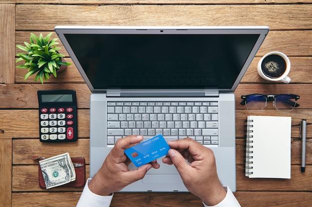 Uomo che tiene la carta di credito e utilizzando il computer portatile.