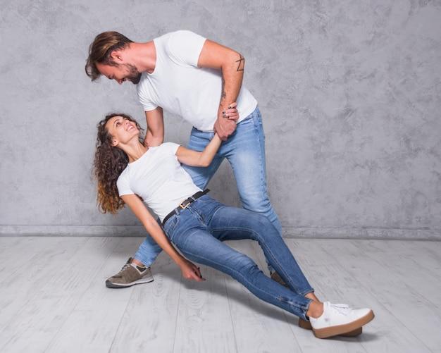 Uomo che tiene la donna che cade sul pavimento