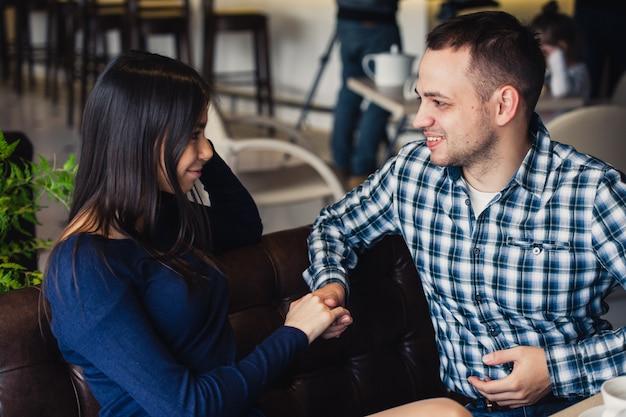 Uomo che tiene la mano della sua ragazza prima di cena