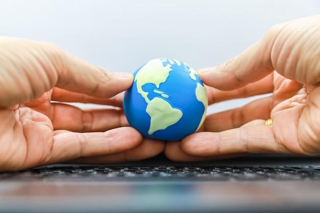Uomo che tiene la mini palla del mondo con il computer tastiera