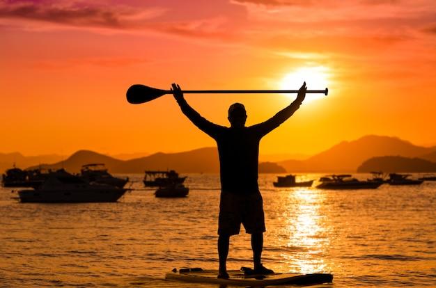 Uomo che tiene la pagaia in cima mentre si alza in piedi al tramonto