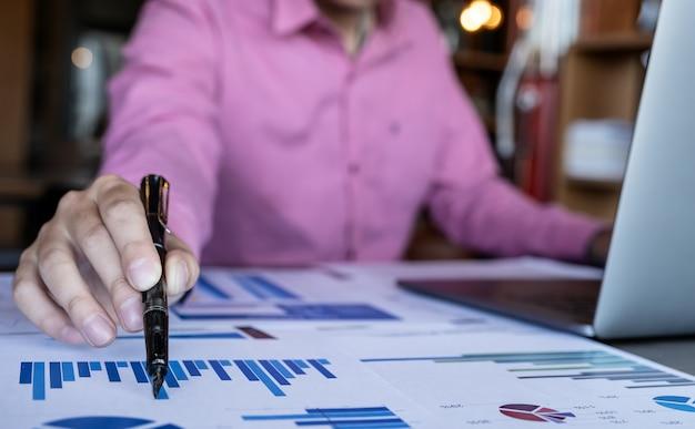 Uomo che tiene la penna mentre si lavora con il computer portatile