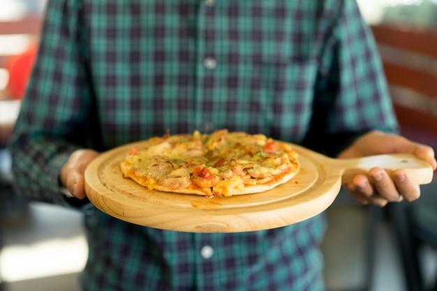 Uomo che tiene la pizza italiana cultura fast food con formaggio e ingrediente sul piatto di legno