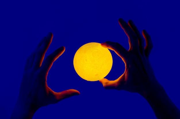 Uomo che tiene la sfera illuminata a forma di luna gialla.