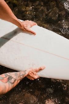 Uomo che tiene la tavola da surf sull'acqua