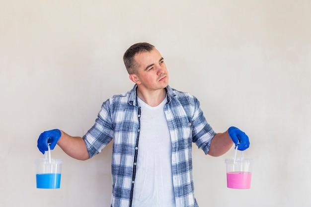 Uomo che tiene la vernice rosa e blu