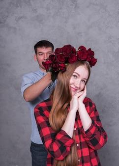 Uomo che tiene le rose sulla testa di donna